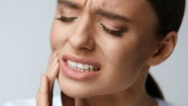 Image of a woman with a severe tooth pain - a common type of dental emergency